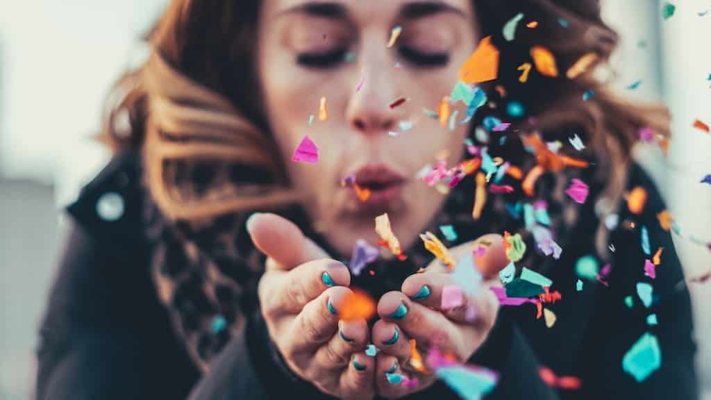 girl blowing confetti
